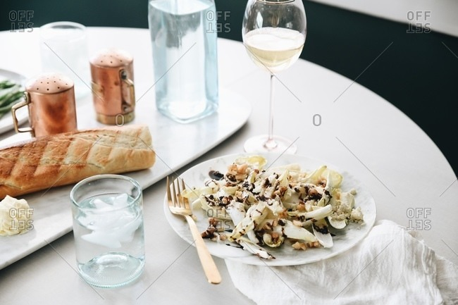 Endive salad with walnuts and blue cheese dressing served on table with wine in a restaurant