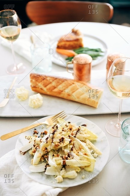 Endive salad with walnuts and blue cheese dressing served on table with quiche Lorraine dish in background in a restaurant