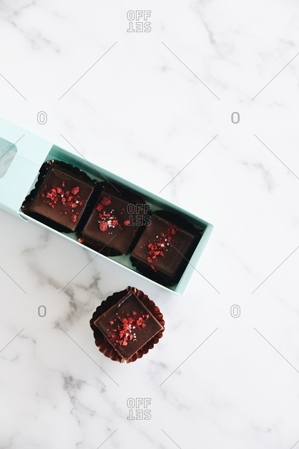 Overhead view of fudge in and beside gift box on marble surface