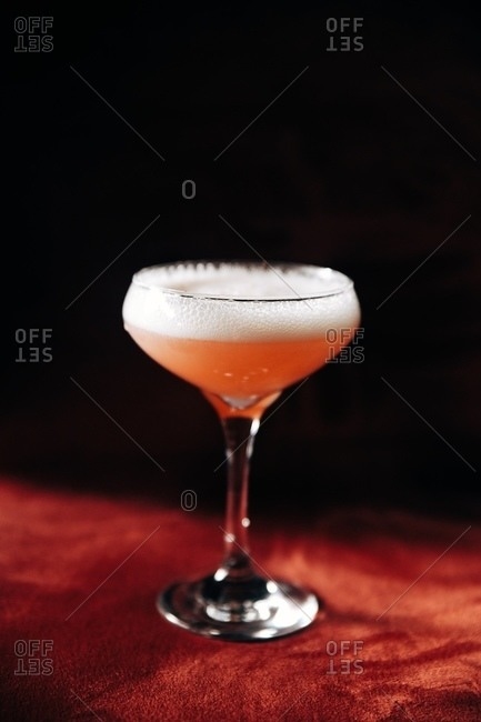Pink foaming cocktail on red surface with black background