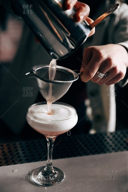 Bartender pouring a pink foaming cocktail on bar top