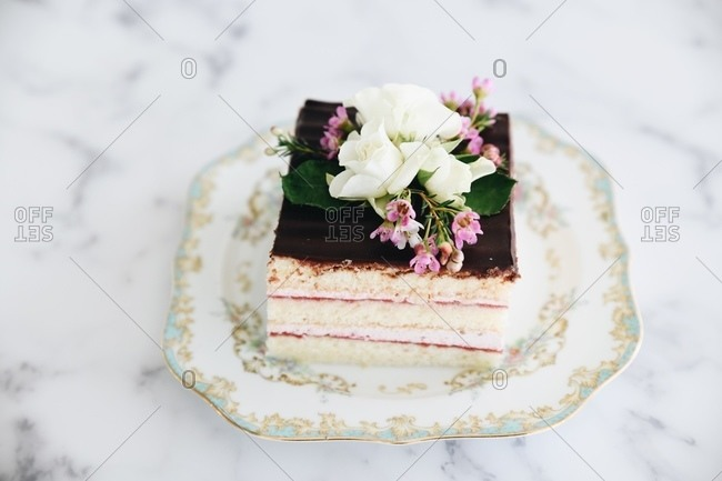 Layered cake topped with chocolate icing and flowers