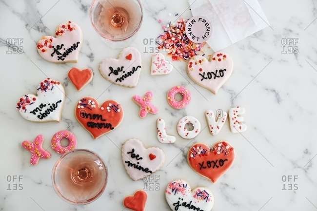 Overhead view of Valentine's Day cookies on white marble surface with blush wine