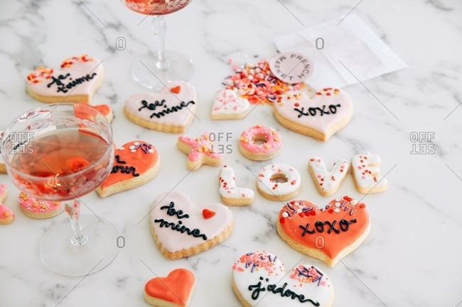 Valentine's Day cookies on white marble surface with blush wine