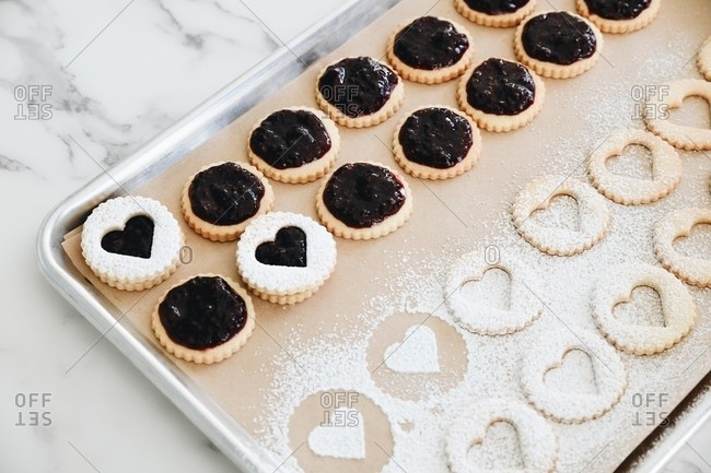 Overhead view of heart Linzer cookies with powdered sugar being prepared on baking tray