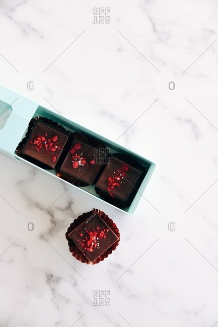 Overhead view of fudge being packaged in a gift box on marble surface