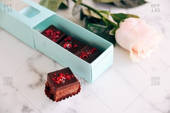 Fudge being packaged in a gift box on marble surface beside a rose