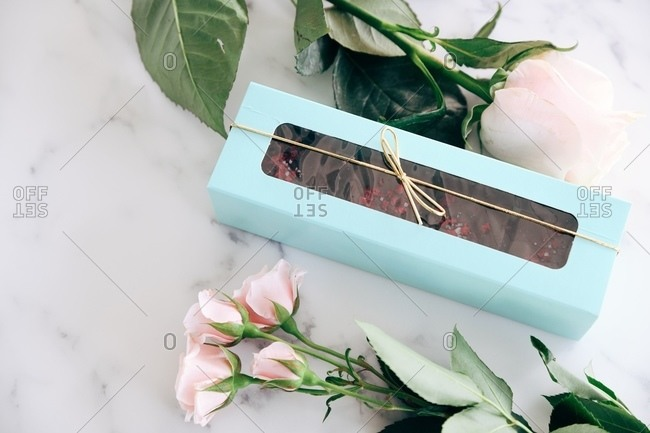 Fudge packaged in a gift box on marble surface beside a rose