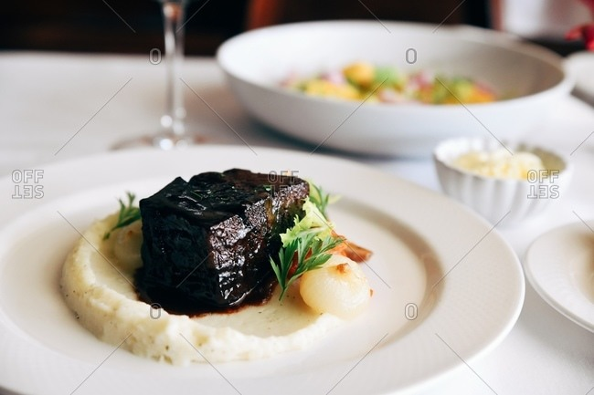 Braised beef short rib served on a bed of celeriac puree with roasted carrot, cippolini onion, red wine jus