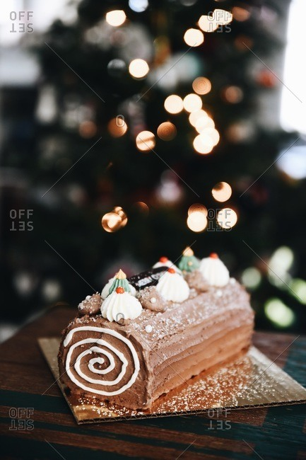 A delicious holiday yule log dessert on table with Christmas tree in background