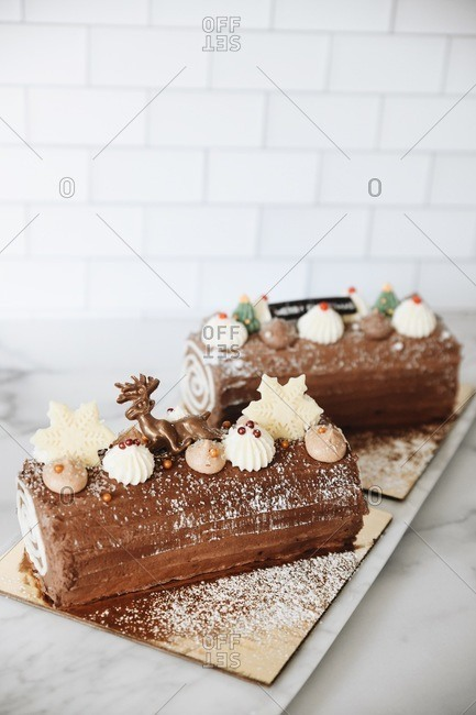 Two chocolate holiday yule logs dessert on marble surface with copy space