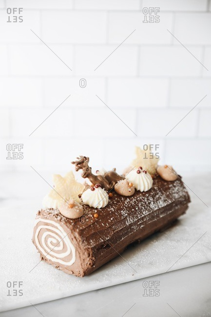 A chocolate holiday yule log dessert topped with a reindeer on marble surface with copy space