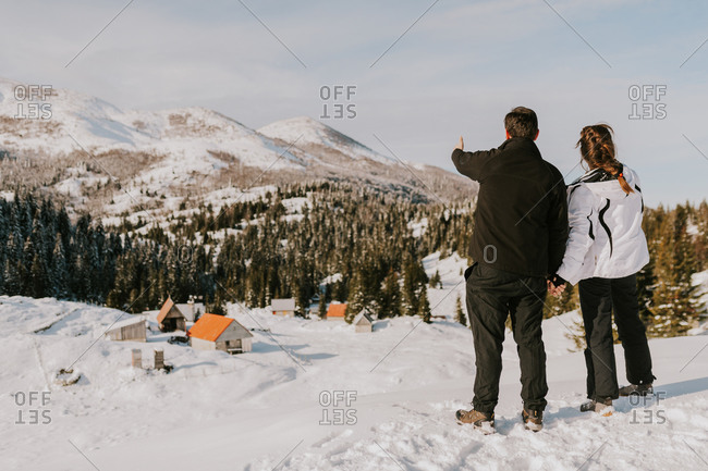 Back view of couple looking out and pointing towards homes in the snowy Bjelasnica mountains in Bosnia and Herzegovina