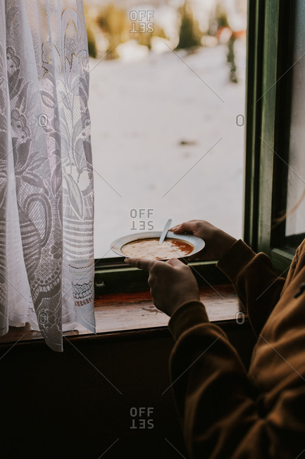 Woman eating soup by window overlooking snowy Bjelasnica mountains in Bosnia and Herzegovina