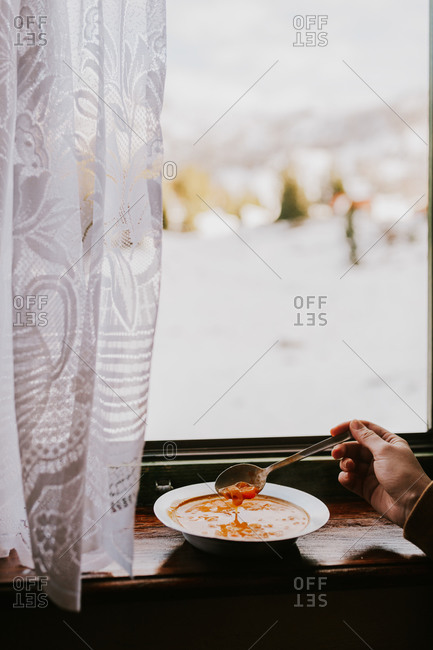 Hand of a woman eating soup by window overlooking snowy landscape in Bosnia and Herzegovina