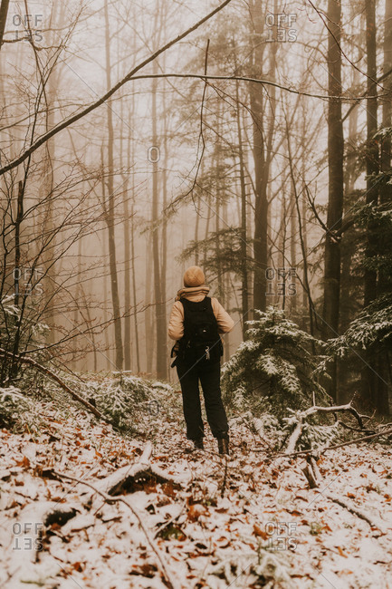 Rear view of woman hiking in a foggy forest in the Bjelasnica mountains in Bosnia and Herzegovina