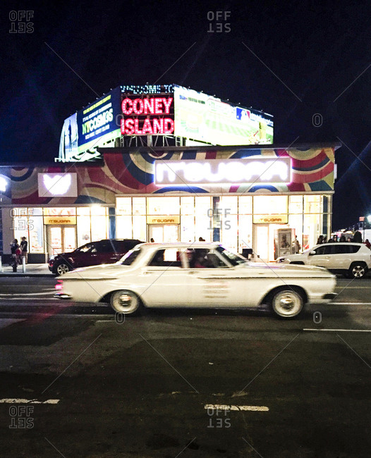 Coney Island, New York: Classic car passing by It's Sugar candy store