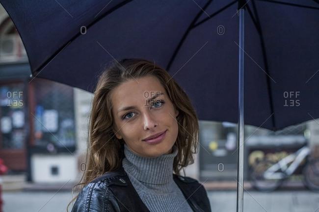 Businesswoman under umbrella on street during rainy season