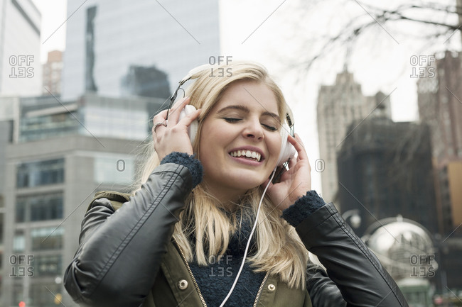 Young woman smiling while listening music in city