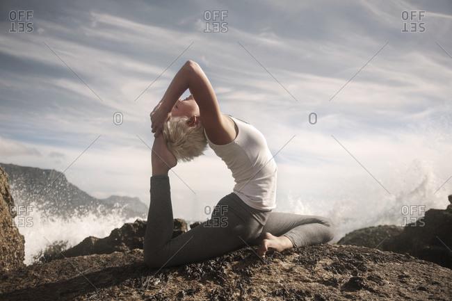 Flexible woman practicing Sirsapada Natarajasana on rock formation