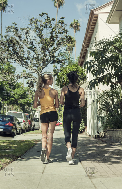 Multi-ethnic friends jogging along streets on sunny day