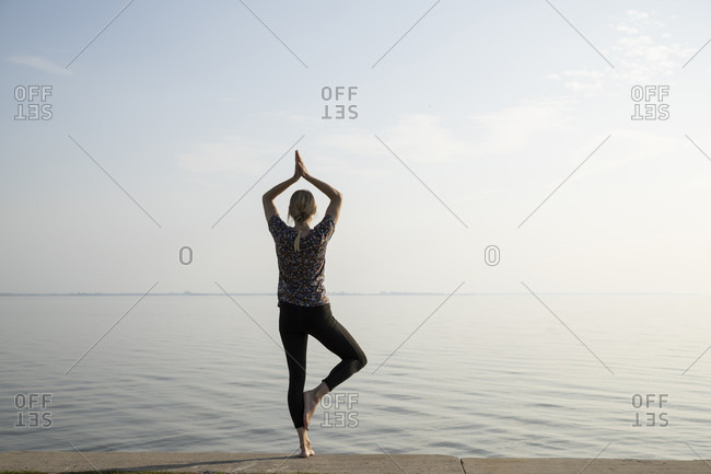 Sportswoman practicing tree pose on promenade at morning