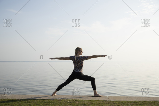 Active woman practicing warrior position at promenade