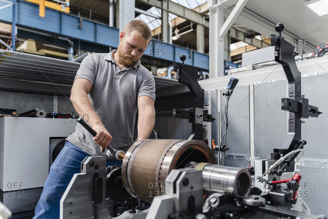 Young industry laborer tightening bolts of machine while standing at factory
