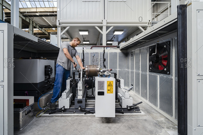 Expertise tightening machine bolts while standing at factory