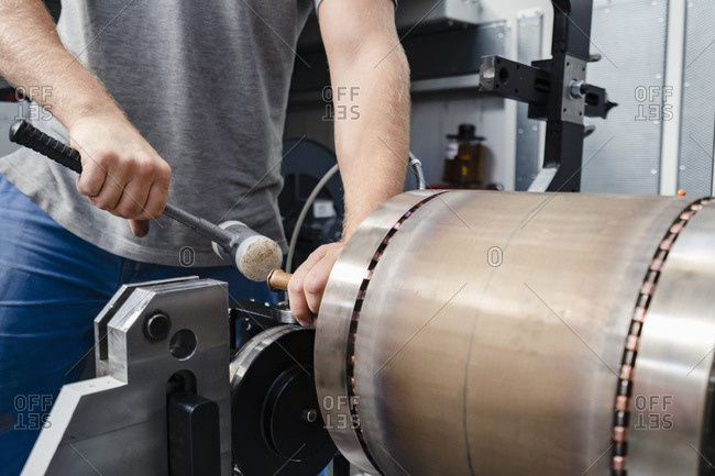 Male industrial laborer hitting hammer on machine part while standing at factory