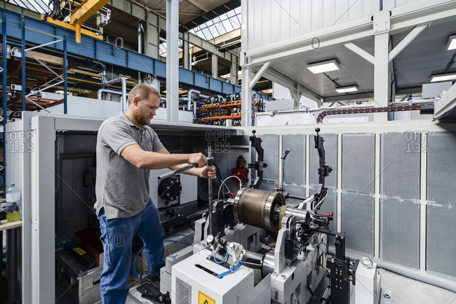 Expertise repairing machine while standing at factory