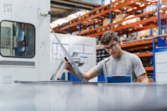 Young male engineer examining product at factory