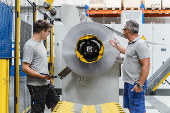 Male colleagues testing machinery in illuminated industry