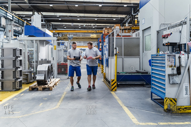 Male manual workers discussing while walking in illuminated factory