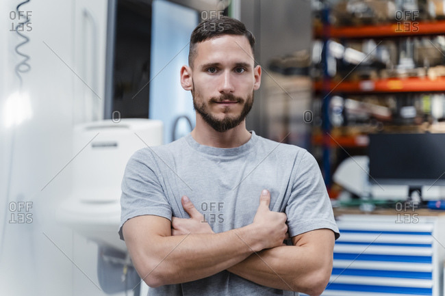 Confident young manual worker with arms crossed standing at industry