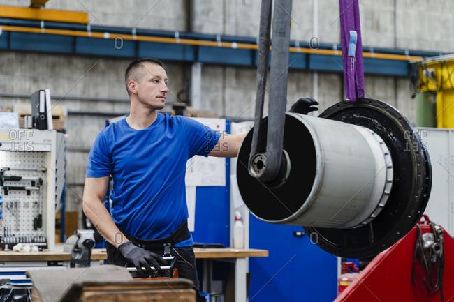 Male manual worker examining machine at illuminated industry
