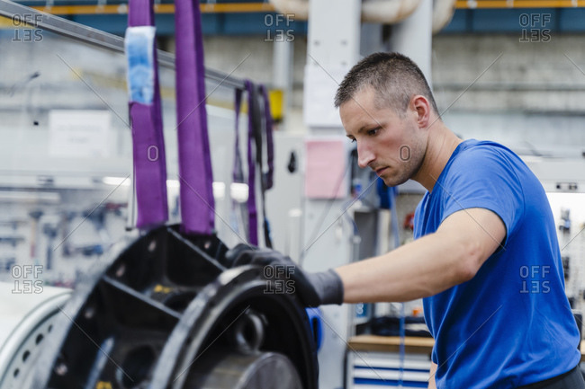 Male manual worker concentrating while doing quality check of machinery at illuminated factory