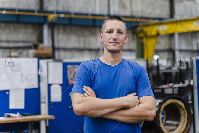 Confident male manual worker with arms crossed standing at industry