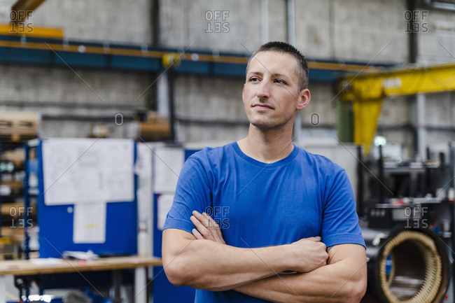 Contemplating male technician looking away with arms crossed at factory