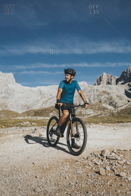 Cyclist with bicycle exploring Picos de Europa National Park on sunny day- Cantabria- Spain
