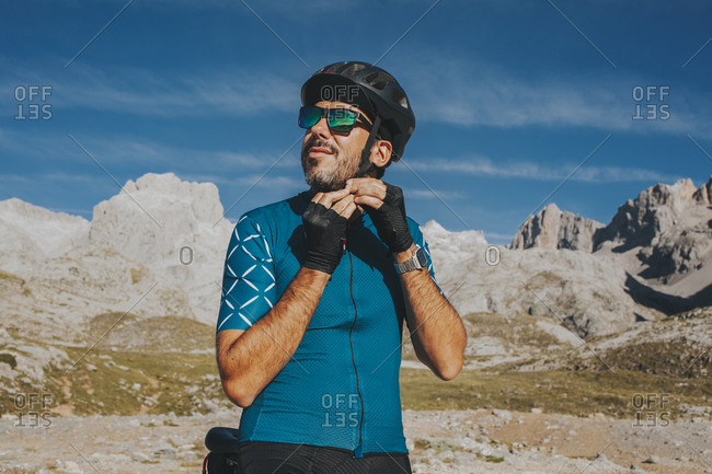 Cyclist adjusting cycling helmet at Picos de Europa National Park on sunny day- Cantabria- Spain