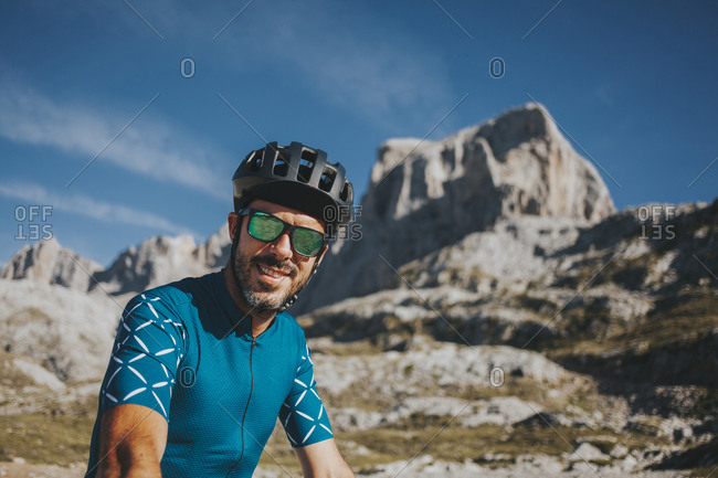Smiling mid adult male cyclist wearing cycling helmet and sunglasses at Picos de Europa National Park- Cantabria- Spain