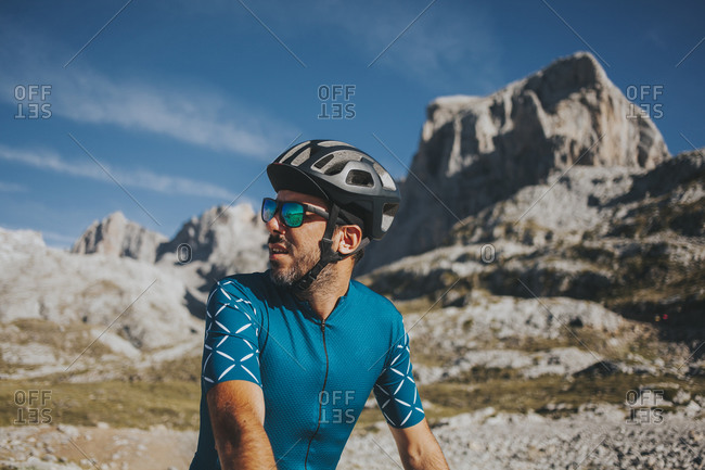 Male cyclist looking away at famous Picos de Europa National Park on sunny day- Cantabria- Spain