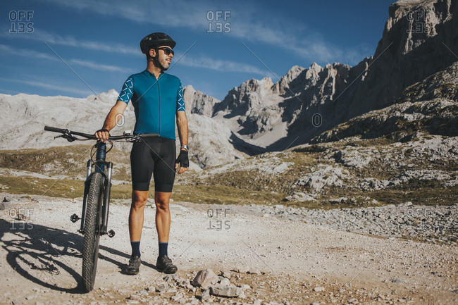 Male cyclist looking away while standing with bicycle at Picos de Europa National Park- Cantabria- Spain