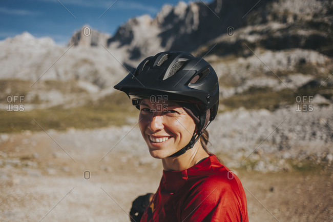 Smiling woman wearing cycling helmet on sunny day- Picos de Europa National Park- Cantabria- Spain