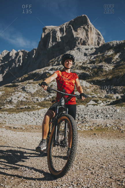 Female cyclist with bicycle against mountain at Picos de Europa National Park- Cantabria- Spain