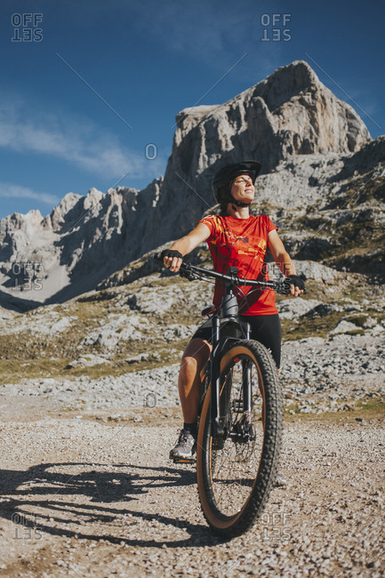 Smiling female cyclist with eyes closed on bicycle at Picos de Europa National Park- Cantabria- Spain