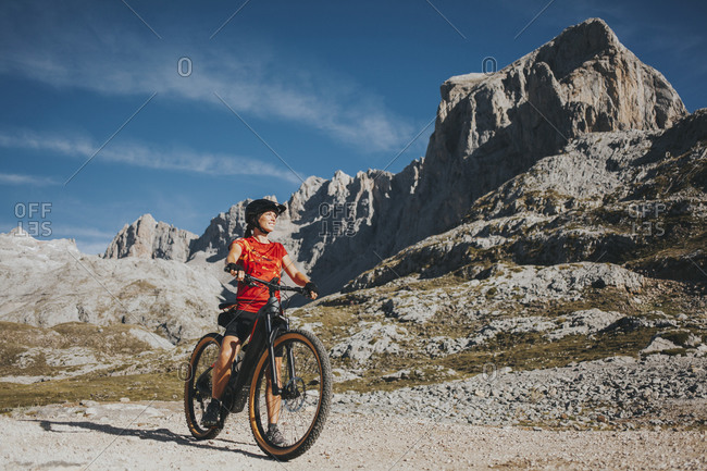 Adventurous cyclist looking away at Picos de Europa National Park during weekend- Cantabria- Spain