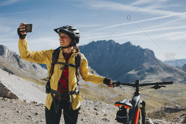 Female cyclist with bicycle taking selfie at Picos de Europa National Park- Cantabria- Spain