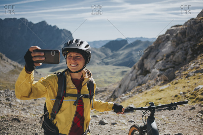Smiling female cyclist taking selfie with mountain bike against mountain- Picos de Europa National Park- Cantabria- Spain